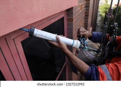 Rope access abseiler handy man building repair commercial services wearing full  safety body harness abseiling applying sealant fixing leaking windows repairing, Sydney CBD, Australia