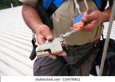Rope access construction worker  inspection maintenance services on safety equipment device connected with locking Karabiner and shock absorber lanyard on roof building site prior to used building sit