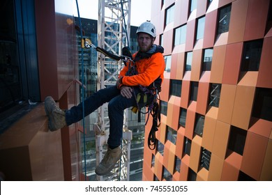 Rope access construction worker wearing safety equipment abseiling, working at hight in Sydney city, Australia