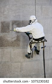Rope access facade maintenance; A worker wearing a protective gear cleaning a stone church exterior with abrasive blasting equipment