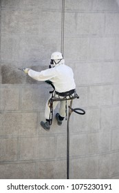 Rope access facade maintenance; A worker wearing a protective gear cleaning a stone exterior with sandblasting equipment