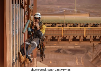 Rope access hard worker miner welder  wearing fully safety body harness equipment abseiling dehydration hanging drinking water during hot summer month construction mine site Pilbara Perth Australia