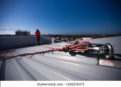 Rope access height safety carabiners connecting with figure of eight knots rigging, clipping into roof fall arrest and fall restraint anchor point systems ready to ascending, construction site Sydney