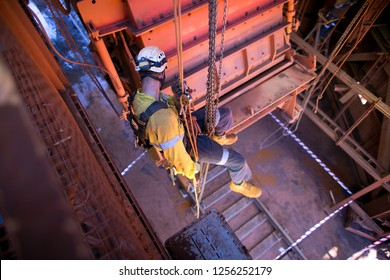 Rope access industrial fitter wearing safety helmet working at height using low stretch static rope safety descending device, descending after completing the task construction site, Sydney, Australia
