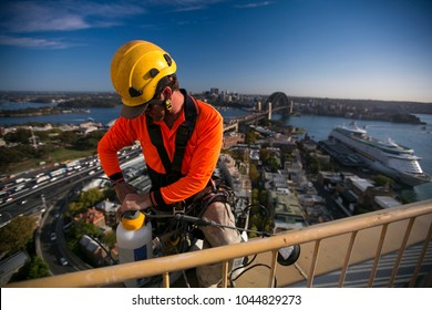 Rope access industrial worker wearing yellow hard hat, long sleeve shirt, safety harness, carrying white bucket, working, abseiling off from the high rise building at circular quay, Sydney, Australia