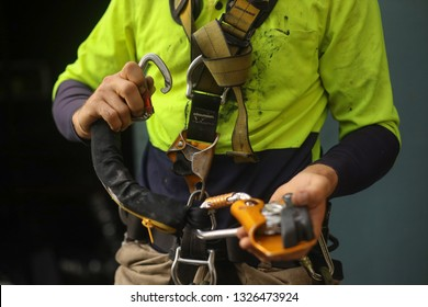 Rope access inspector clipping locking Karabiner into front of full body safety abseiling harness loop with self controlled stop a fall descent safety device  absorbing lanyard attached at the end