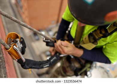 Rope access inspector industrial abseiler wearing full body safety abseiling harness  using self controlled stop a fall descent safety back up device with absorbing lanyard attached while abseiling