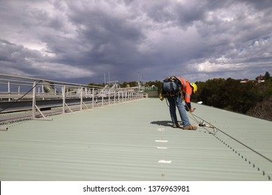 Rope access inspector technician using his phone taking pictures fall arrest, fall restraint roof anchor point horizontal safety line while conducting safety inspecting Sydney, CBD, Australia