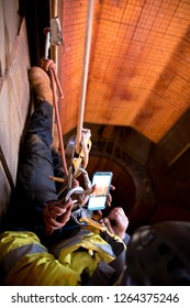 Rope access mine inspector wearing full body safety harness working at height abseiling using mobile phone taking pictures while commencing NDT thickness inspection construction site, Perth Australia
