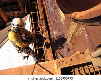 Rope access miner abseiling working at height on rope using shovel removing contaminated grease at construction mine site Perth, Australia