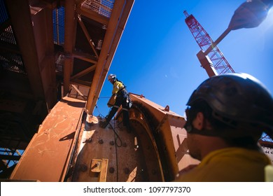 Rope access miner fitters, boilermaker working at height wearing full safety equipment abseiling while his partner doing supervision making sure is safe construction mine site Perth, Australia