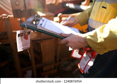 Rope access miner supervisor inspecting and checking name list on isolation permit holder box ensure all construction miners are locking on right permit prior to work on mine site, Perth, Australia