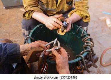 Rope access miner technician inspector inspecting cleaning safety descenders, screw gate locking carabiners hardware equipment making sure are safe and good condition prior work at construction site