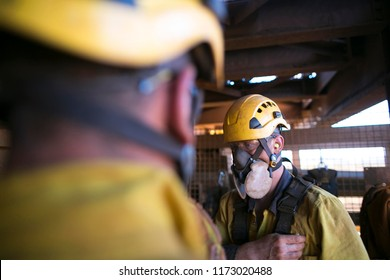 Rope access miner welder preparing using safety dust protection P3 mask before working in confined space at construction site Perth, Australia