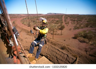 Rope access miner welder worker wearing fully safety equipment abseiling and sorting clipping his hard ling device into back up rope ready to weld on construction mine site Perth Western of Australia