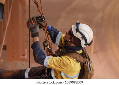 Rope access miner welder worker wearing fully safety equipment abseiling and sorting clipping inspecting his back up device into rope ready to abseiling down  construction mine site Perth, Australia