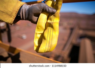 Rope access rigger high risk worker wearing heavy duty glove holding inspecting a yellow three lifting sling in Sydney city Construction building site, Australia