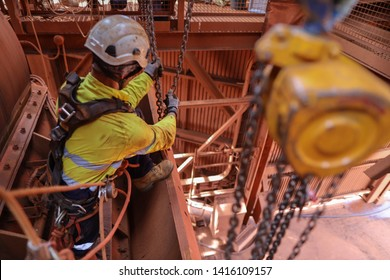 Rope access rigger wearing harness safety helmet heavy duty glove abseiling working in fall arrest position commencing using a lifting chain block hoist lifting a heavy load at construction site WA