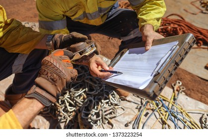 Rope access technician abseiler conducting safety inspecting check list serial number on ascender prior used during shut down operation mine site Pilbara region, Perth, Australia
