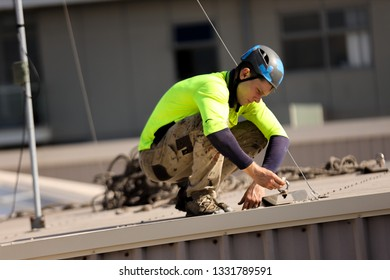 Rope access technician abseiler wearing a safety helmet long sleeve shirt abseiler conducting safety inspecting roof anchor tag prior using abseiling building site Sydney, Australia