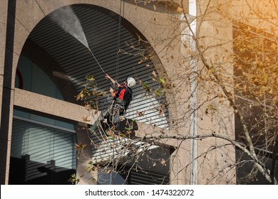 Rope access technician abseiler wearing full safety harness helmet working at height with twin rope abseiling performing high pressure windows building structure cleaning at hight rise building SYD