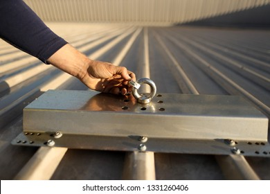 Rope access technician hand conducting safety inspecting roof anchor tag prior using abseiling building site Sydney, Australia