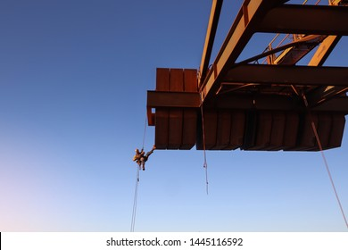 Rope access technician inspector abseiler working at height abseiling and organising tools lanyard preventing from dropped object during concrete spalling inspection on counterweight construction site