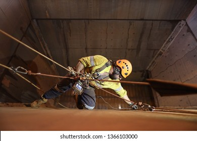 Rope access technician inspector Non Destructive Testing (NDT) wearing fall body safety harness, safety helmet abseiling and precisely conducting chute bin inspection, Perth mine site, Australia