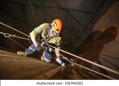 Rope access technician inspector Non Destructive Testing (NDT) wearing fall body safety harness, safety helmet precisely conducting chute bin preparation prior inspection, Perth mine site, Australia