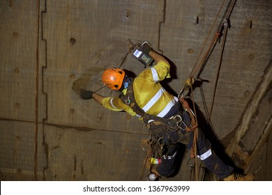 Rope access technician inspector Non Destructive Testing (NDT) wearing fall body safety harness, safety helmet abseiling in Y hang position conducting chute bin inspection, Perth mine site, Sydney