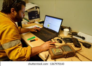 Rope access technician inspector Non Destructive Testing (NDT) setting on the chair precisely conducting chute bin  inspection report with NDT unit beside him during shut down operation, Perth