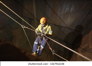 Rope access technician Non Destructive Testing (NDT) wearing fall body safety harness, safety helmet conducting rope transferring during performing chute bin inspection, Perth mine site, Australia