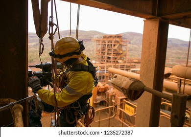 Rope access technician wearing safety harness, abseiling with twin rope working at height commencing electric magnet drilling into the structure wall construction mine site Perth
