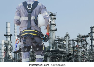Rope access technician wearing safety harness standing on beam structure in fall restraint position securing with into safety line commencing clipping descender into tie line construction on refinery