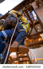 Rope access technicians rescuer  performing lifting casualty by standing up on leg loop to snatch remove rope out from chest ascender device, mean time beware safety of casualty by don't dropping them
