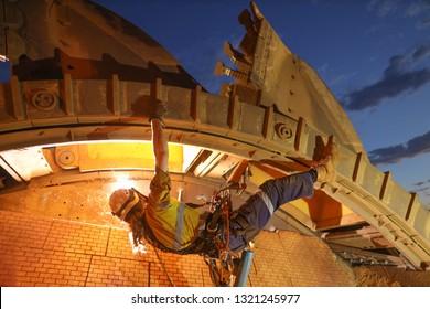 Rope access welder maintenance abseiler wearing fall safety body harness helmet protection hanging upside down welding repairing reclaimer wheels bucket construction mine site Perth, Australia