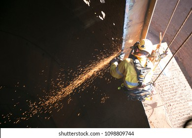 Rope access welder wearing full safety body harness, face shield protection and working at height, abseiling using electricity power tool grinding preparing metal construction 9/5/18 Perth, Australia