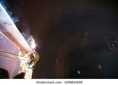 Rope access welder wearing full safety body harness, face shield protection and working at height, abseiling and welding metal plate on mining construction site 9/5/18 Perth, Australia