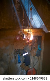 Rope access welder wearing safety equipment abseiling hanging on harness as fall arrest position welding repairs, maintenance in confined space area work on construction site Perth, Australia
