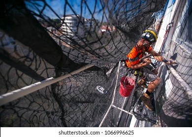 Rope access worker abseiling working in enclose of industry net full arrest protection wearing full protection dust mask, safety harness working removing concrete on construction site, in Australia