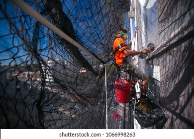 Rope access worker abseiling working in enclose of industry net full arrest protection wearing full protection dust mask, safety harness working grinding concrete on construction site, in Australia