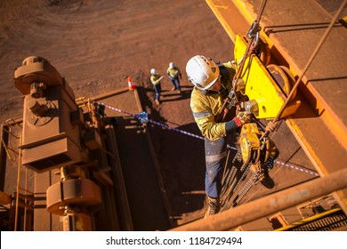 Rope access worker wearing safety harness hard hat working at height descending on rope performing installing lifting chain block into beam clamp trolley structure construction site Perth, Australia