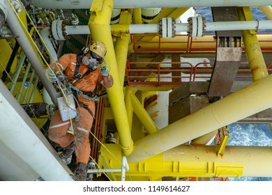 Rope access. Working at height. A commercial abseiler with fall arrestor device hanging at the edge of oil and gas platform looking up for painting activities.
