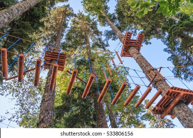 Rope adventure park in a summer forest scenic blue sky scenery. Overcoming obstacles and reaching heights abstract concept