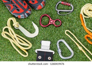 rope, belt and climber shoes are on the grass