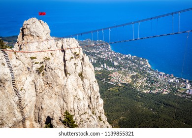 Rope bridge above chasm on Mount Ai-Petri overlooking Black Sea coast, Crimea, Russia. This place is a scenic landmark of Crimea. Amazing view of cliff with rope bridge over abyss in Southern Crimea.