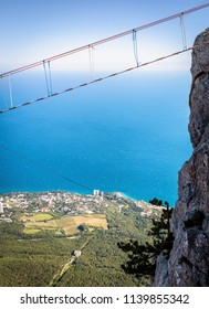 Rope bridge on the Mount Ai-Petri above chasm, Crimea, Russia. This mountain is one of the main tourist attractions of Crimea. Hanging bridge over abyss on the Black Sea coast of Crimea in summer.