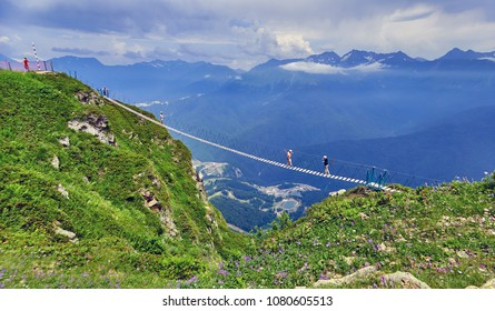 Rope bridge in Sochi mountains with tourist girls in sunny day in Rosa Khutor