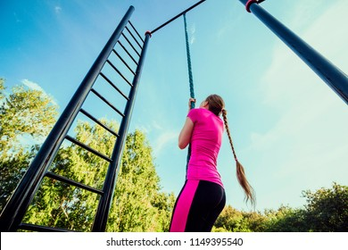 Rope climbing outdoors. Girl in pink sportswear doing exercises at street workout place in summer morning. Healthy lifestyle sport concept