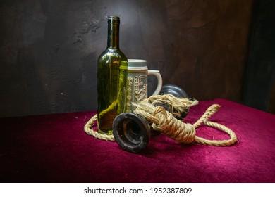 Rope, empty wine bottle on red velvet